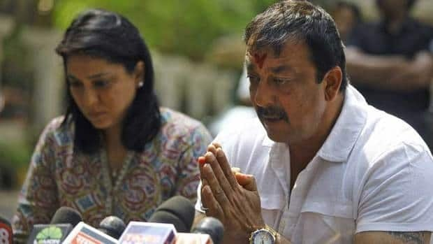 Bollywood star Sanjay Dutt, right, gestures to the media after breaking during a press conference in Mumbai on Thursday. His sister, politician Priya Dutt, supported him as he announced he would return to jail as ordered.