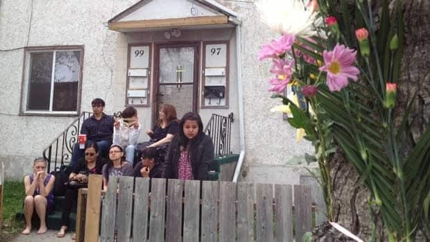 Some of the 15 to 20 people who gathered for a vigil Thursday afternoon sit outside the Lorne Avenue rooming house where Myrna Letandre's remains were found.
