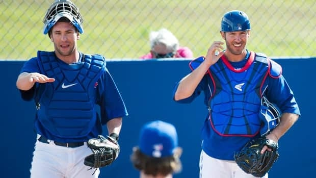 Toronto Blue Jays catchers Josh Thole, left, and J.P. Arencibia, right, are among the candidates to handle the bulk of starts for knuckleballer R.A. Dickey, centre.