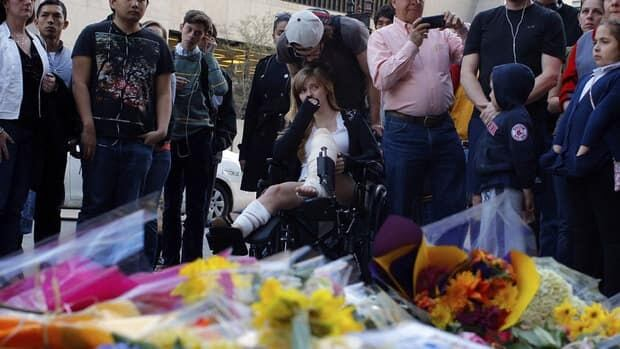 A Boston Marathon bombing survivor (centre) visits the site of the first bomb explosion on Boylston Street in Boston, Massachusetts April 24, 2013.