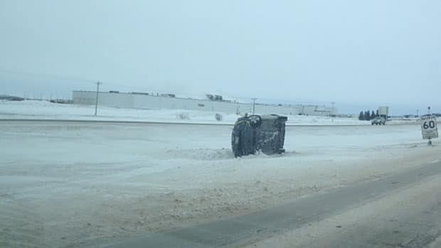 A car lies on its side off the Trans-Canada Highway near Portage la Prairie.