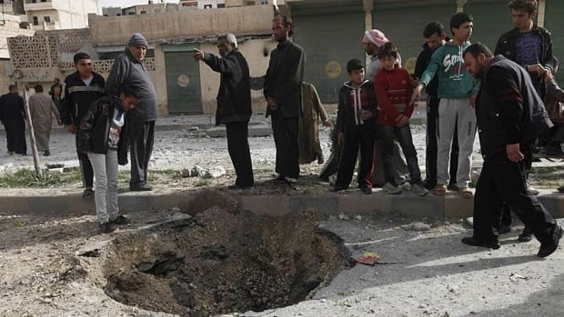 Civilians inspect a bomb crater after what activists said were missiles fired by a Syrian Air Force fighter jet loyal to President Bashar al-Assad in Raqqa province, eastern Syria.