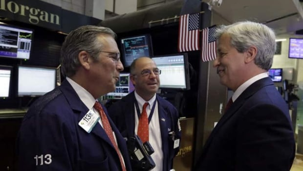 JPMorgan Chase Chairman and CEO Jamie Dimon, right, visits with  traders Thomas Kay, left, and Frederick Reimer on the floor of the New York Stock Exchange Friday.The biggest U.S. bank, says its second-quarter earnings surged 32 per cent.