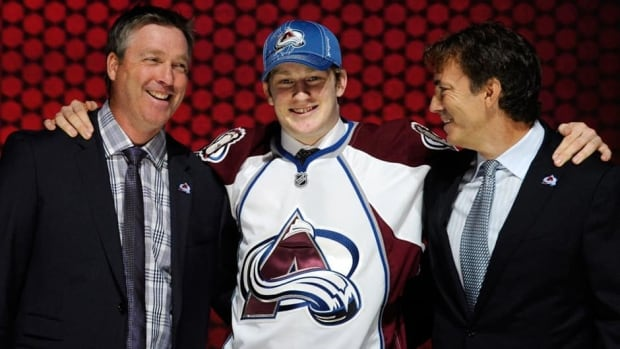 Nathan MacKinnon, centre, stands with Patrick Roy, left, and Joe Sahkic, right, of the Colorado Avalanche after being chosen 1st overall at the  NHL Entry Draft on Sunday in Newark, N.J.