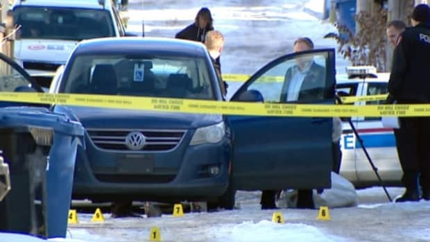 Investigators search the vehicle where a body was found in northeast Calgary on Monday morning.