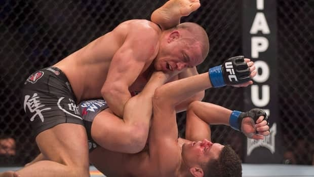 Georges St-Pierre, left, pins Nick Diaz to the canvas during their UFC 158 title fight Saturday in Montreal.