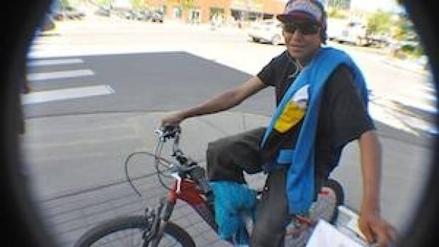 Chris Sterriah of Whitehorse says he's nonchalant about the bylaw: On a sunny Friday we found him on the sidewalk with no helmet and earphones. To be fair, he was chatting with friends and using the bike as a seat. (Philippe Morin/CBC)
