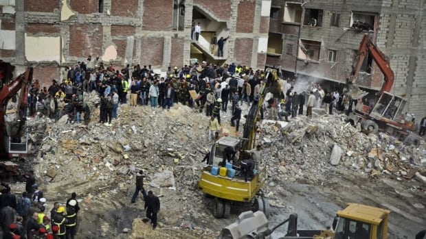 Egyptians stand in rubble after an eight-storey building collapsed in Alexandria on Wednesday.