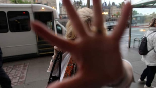 Pamela Wallin blocks Dave Chan's camera with her hand as she enters her Ottawa office.