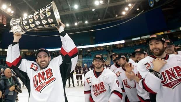 University of New Brunswick Varsity Reds forward Colby Pridham hoists the University Cup trophy after defeating the Saint Mary's Huskies in the 2013 CIS University Cup hockey final Sunday in Saskatoon.