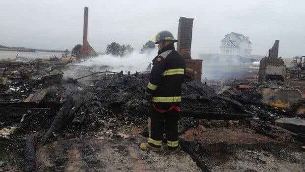 A firefighter inspects the smouldering remains of the Stanhope Beach Resort.