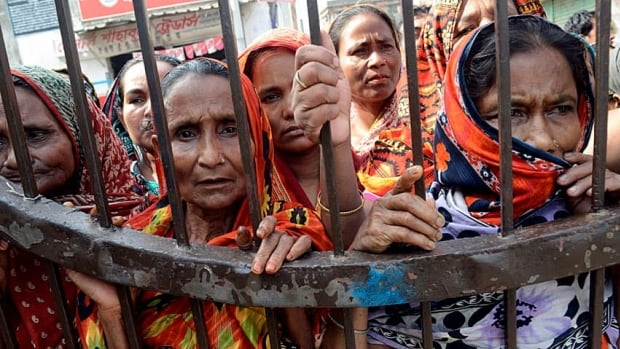 Women watch from behind a gate while unclaimed bodies are brought to a cemetery from the garment factory building collapse in preparation for a mass burial in Dhaka, Bangladesh.