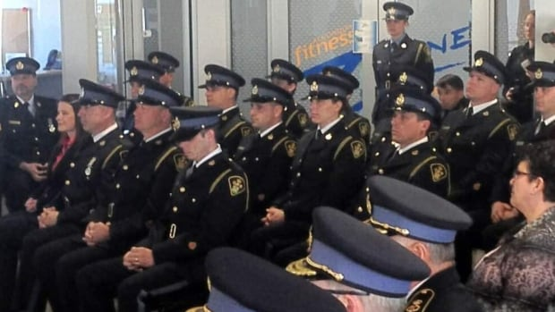 Former Perth Police Service officers are sworn in as members of the OPP on Saturday at Algonquin College's Perth campus.