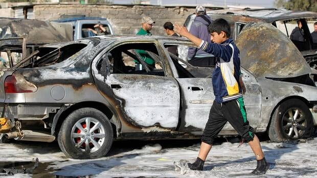 A boy walks past a burnt vehicle at the site of a bomb attack in the Shuala district in Baghdad on Tuesday. The parked car bomb exploded in a crowded Shia market killing 5 people and wounding 13 others.