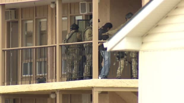 Police take a man into custody on Wednesday at a motel in Two Hills, Alta.