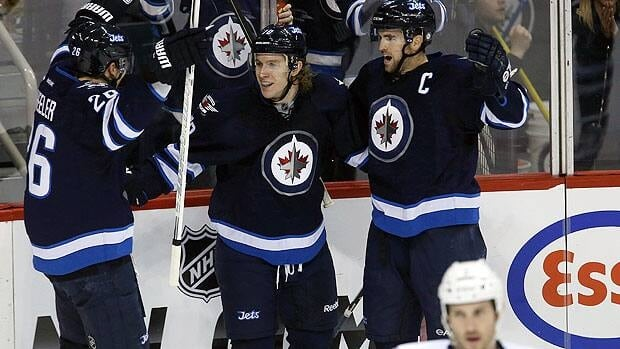 Winnipeg Jets' Blake Wheeler (26), Bryan Little (18) and Andrew Ladd (16) celebrate after Little opened the scoring against the Tampa Bay Lightning during first period NHL hockey action in Winnipeg on Sunday, March 24, 2013.