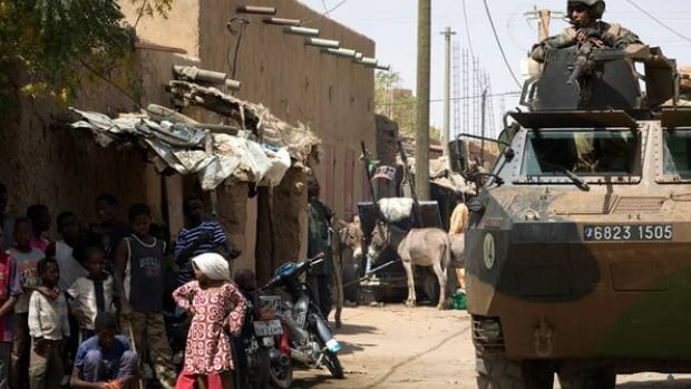 French soldiers patrol a street on Thursday in the northern Mali's largest city Gao. Officials say troops could be in the West African country until at least July.