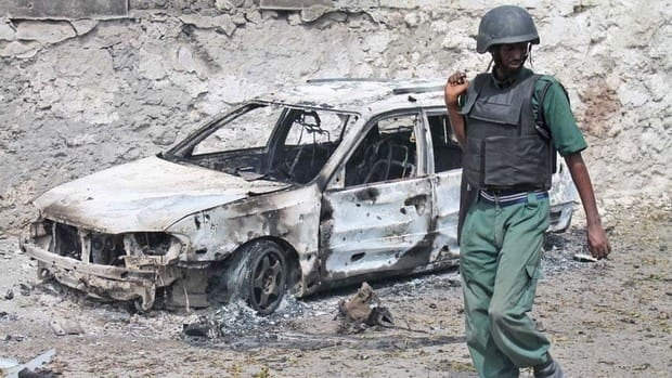 A Somali soldier walks near a destroyed car near the entrance of Mogadishu's court complex on Sunday.