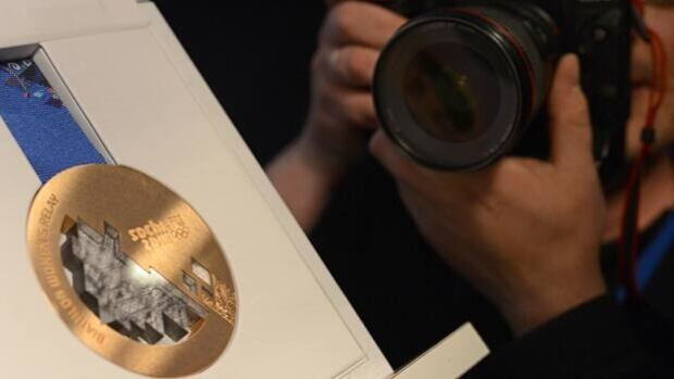 A photographer snaps pictures of a bronze medal to be awarded at the 2014 Sochi Olympics.