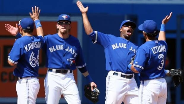 Munenori Kawasaki, left, Colby Rasmus, Rajai Davis and Maicer Izturis celebrate Toronto's 13-5 rout of Baltimore on Sunday.