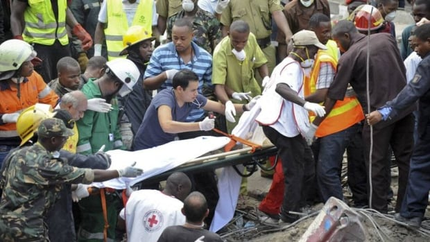 Rescuers from the Tanzania Red Cross carry away a body from the rubble of a collapsed building in downtown Dar es Salaam, Tanzania. A police official says the multi-storey building was in the final stages of its construction and most of the people caught up in the collapse were passing by.