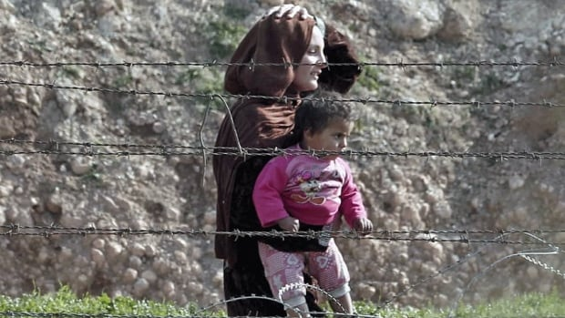 A Syrian woman from the northern Syrian town of Ras al-Ain carries her child at the Turkish border. The Syrian government has called on all citizens to return home, as part of President Bashar al-Assad's bid to end a conflict with rebel fighters calling for his ouster.