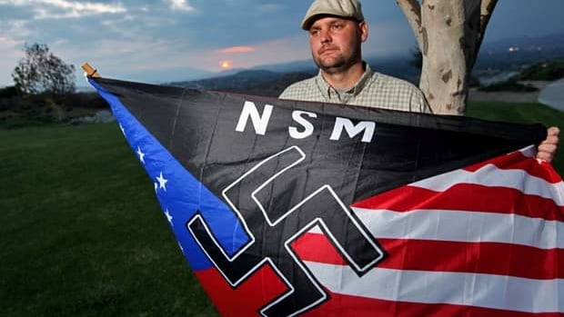 In this October 2010 file photo, Jeff Hall, who was killed by his son, holds a neo-Nazi flag while standing at Sycamore Highlands Park near his home in Riverside, Calif.