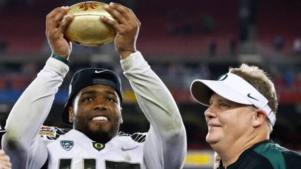 Michael Clay of the Oregon Ducks, left, holds up the championship trophy as head coach Chip Kelly looks on after the Fiesta Bowl against Kansas State on Thursday in Glendale, Ariz. Oregon defeated Kansas State 35-17.