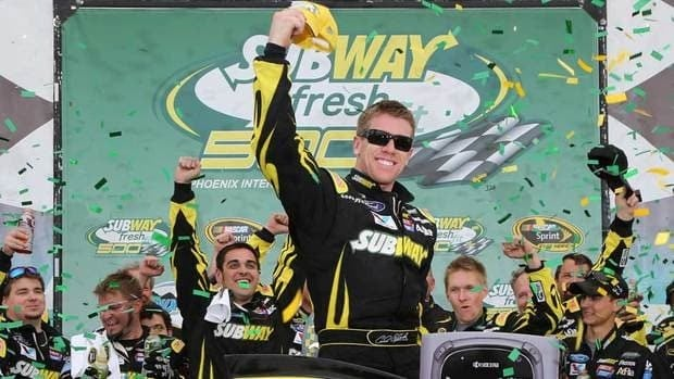 Carl Edwards, driver of the #99 Subway Ford, celebrates in victory lane after winning the NASCAR Sprint Cup Series Subway Fresh Fit 500 at Phoenix International Raceway on Sunday in Avondale, Ariz.