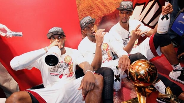 Miami Heat's LeBron James, left, Dwyane Wade, centre, and Chris Bosh sit with the Larry O'Brien Trophy after their team won the NBA title on Thursday.