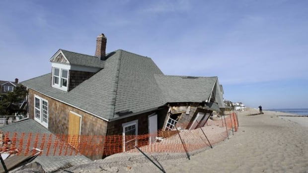 A man photographs a Bay Head, N.J., beach front home that was severely damaged two months ago by Superstorm Sandy.
