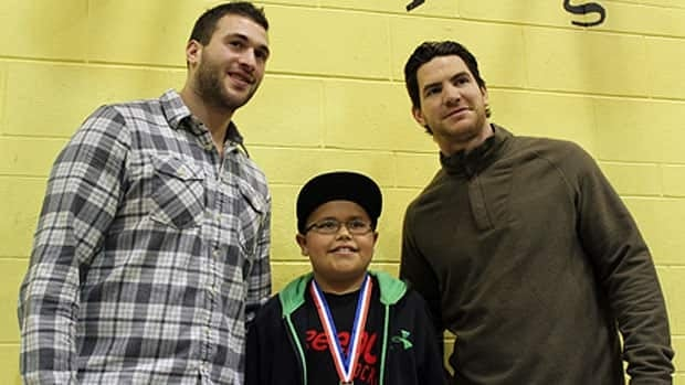 Jets forwards Anthony Peluso (left) and Jim Slater (right) pose with a player from the Norquay Knights on Sunday.