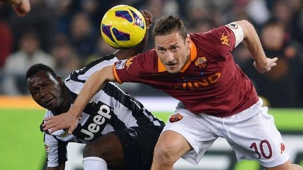 Juventus' Kwadwo Asamoah, left, and AS Roma's Francesco Totti challenge for the ball on Saturday. Struggling Roma upset the visitors.
