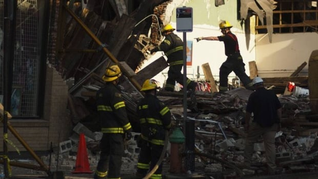 Firefighters search through rubble following the building collapse in Philadelphia. Six people were killed in the collapse.