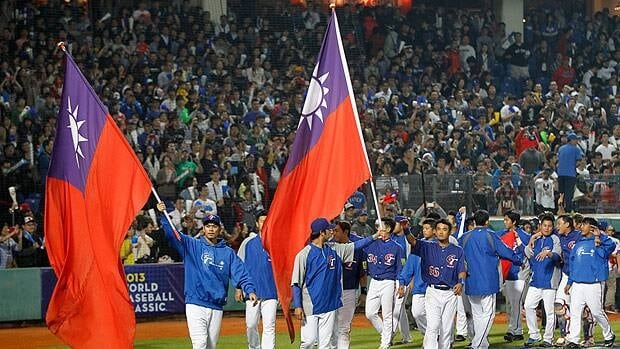 Taiwan celebrates with national flags following their win at the Intercontinental Baseball Stadium in Taichung, Taiwan.