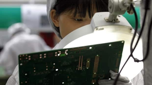 A worker examines a circuit board inside a Foxconn factory in southern Guangdong in this 2010 photo. Chinese police detained a manager at a different factory this week over bribery allegations.