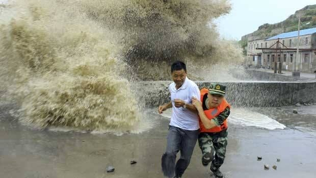A frontier soldier helps a man escape from waves ahead of Typhoon Soulik in Wenzhou, China. The storm battered Taiwan before moving to southeast China Saturday.