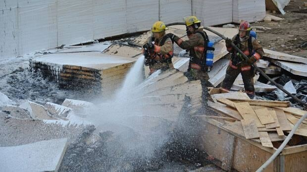 Iqaluit firefighters spray stacks of insulation that caught fire at a construction site Wednesday evening.