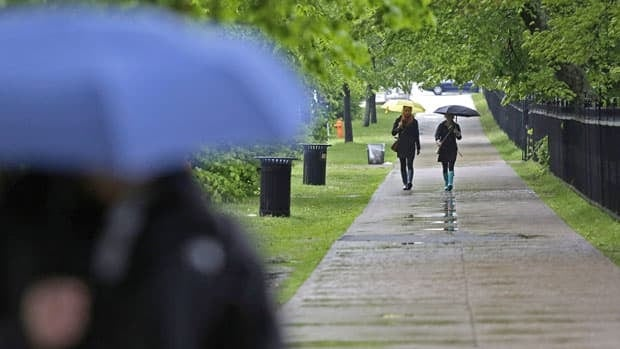 Pedestrians shield themselves from the rain in downtown Halifax, N.S. on Saturday, June 8, 2013. Post-Tropical Storm Andrea is expected to bring over 60mm of rain to Atlantic Canada this weekend.