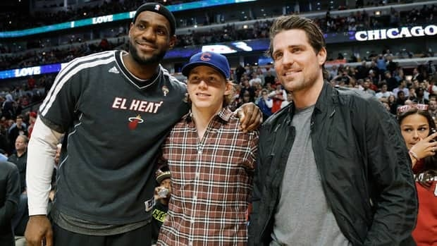 Miami Heat forward LeBron James, left, and Chicago Blackhawks' Patrick Kane, centre, and Patrick Sharp pose for a photo before Wednesday's game against the Chicago Bulls.