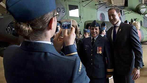 Defence Minister Peter MacKay has his photo taken with members of the military in front of a new Chinook CH-147F helicopter Thursday. MacKay says he wants to remain in the defence portfolio in any cabinet shuffle.