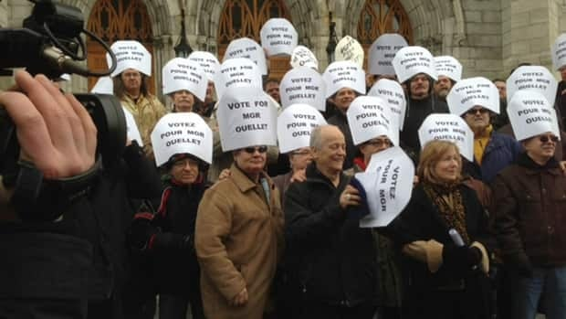 Protesters wore white hats urging the election of Marc Ouellet as the next Pope.