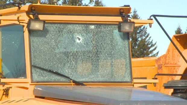 Trucks left at the Trans-Canada Highway construction project appear to be struck by gun fire.