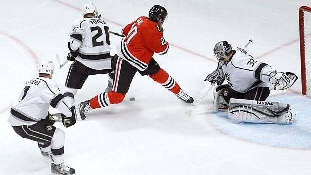 Los Angeles Kings defenseman Slava Voynov (26), of Russia, keeps Chicago Blackhawks left wing Brandon Saad from getting a shot on goal as Rob Scuderi (7) and goalie Jonathan Quick watch during an NHL hockey game on March 25 in Chicago.