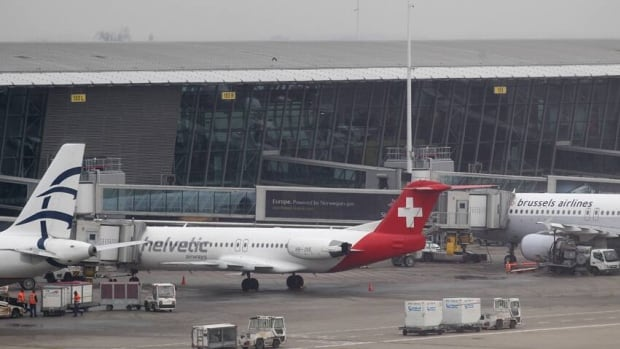 Baggage carts make their way past a Helvetic Airways aircraft from which millions' of dollars worth of diamonds were stolen on the tarmac of Brussels international airport on Tuesday.
