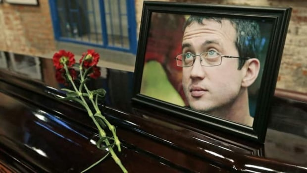 A portrait of Alexander Dolmatov is on display during a memorial ceremony in Moscow. The opposition parter member's death is under investigation.