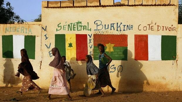Malian girls smile as they walk past a wall decorated with flags of African countries participating in operation Serval in Gao, northern Mali.