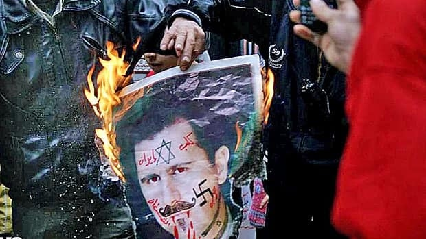 Anti-regime protestors in the Syrian city of Aleppo burn a poster of President Bashar al Assad on Monday.