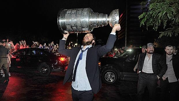 Chicago Blackhawks defenceman Brent Seabrook carries the Stanley Cup past a cheering crowd outside Harry Caray's Restaurant in Rosemont, Ill., early Tuesday.