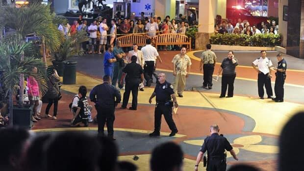 Officers secure the scene Tuesday after Chad Ryan De Soto allegedly drove a Toyota Yaris through a crowd of people in the island's visitor district in Tumon, Guam, crashed into an ABC Store and stabbed several individuals. Three people are dead and 11 are injured.